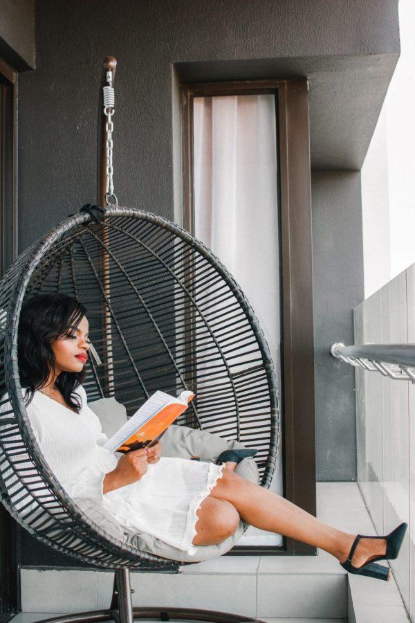 woman sitting in hammock reading