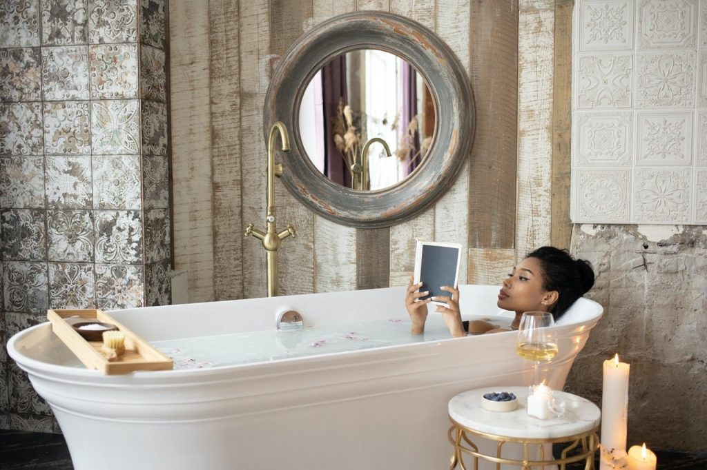women in bath relaxing while reading a book